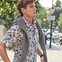 Oliver Cheshire wearing a printed shirt with a jumper round his shoulders