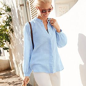 Woman wears white trousers and blue linen shirt