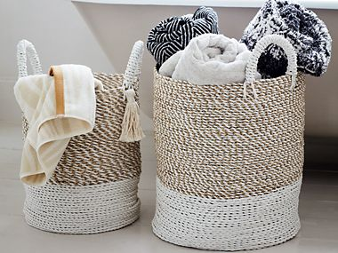 Two bathroom storage baskets with towels inside