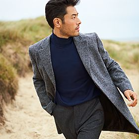 Man wearing grey trouser and coat on a beach