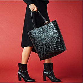 Woman wearing a black mock-croc tote bag and black leather ankle boots