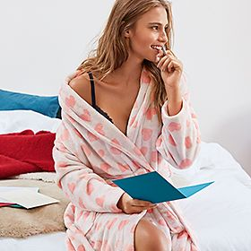 Woman wears a heart-print dressing gown
