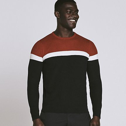 Man wearing block-colour red, white and navy cotton jumper