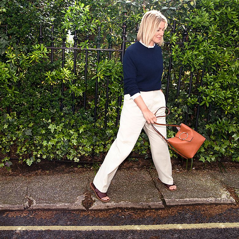 Harriet wearing white linen trousers and navy jumper