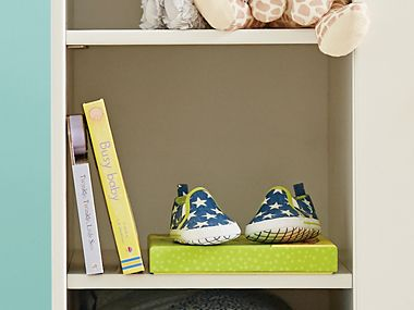Baby shoes and books on a shelf